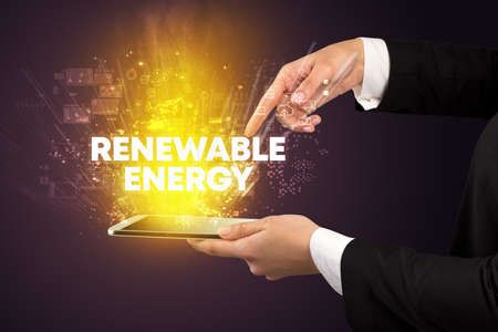 Close-up of a touchscreen with RENEWABLE ENERGY inscription, innovative technology concept
