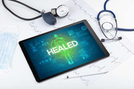 Tablet pc and doctor tools with HEALED inscription, coronavirus concept Stock fotó