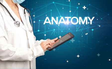 Doctor fills out medical record with ANATOMY inscription, medical concept
