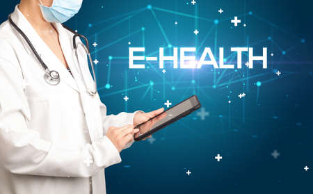 Doctor fills out medical record with E-HEALTH inscription, medical concept
