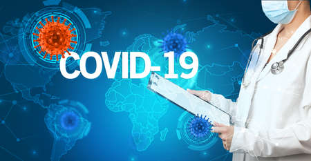 Doctor fills out medical record with COVID-19 inscription, virology concept Reklamní fotografie