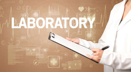 young doctor writing down notes with LABORATORY inscription, healthcare concept