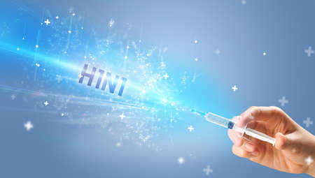 Syringe, medical injection in hand with H1N1 inscription, medical antidote concept