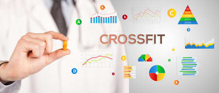 Nutritionist giving you a pill with CROSSFIT inscription, healthy lifestyle concept