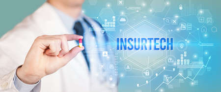 Doctor giving a pill with INSURTECH inscription, new technology solution concept