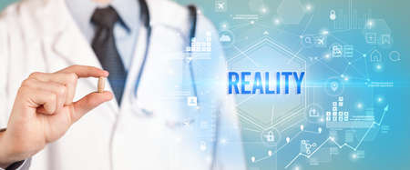 Doctor giving a pill with REALITY inscription, new technology solution concept Reklamní fotografie
