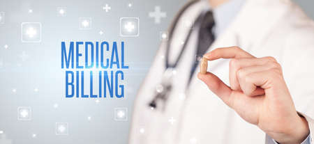 Close-up of a doctor giving a pill with MEDICAL BILLING inscription, medical concept
