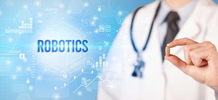 Doctor giving a pill with ROBOTICS inscription, new technology solution concept Reklamní fotografie