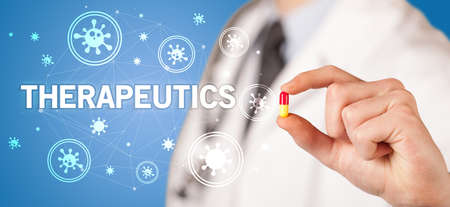 Doctor giving pill with THERAPEUTICS inscription, coronavirus concept