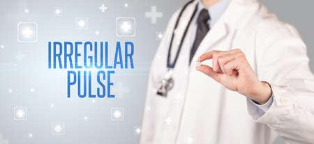 Close-up of a doctor giving a pill with IRREGULAR PULSE inscription, medical concept Reklamní fotografie