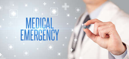Close-up of a doctor giving a pill with MEDICAL EMERGENCY inscription, medical concept