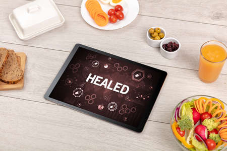 Healthy Tablet Pc compostion with HEALED inscription, immune system boost concept Imagens