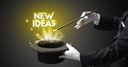 Illusionist is showing magic trick with NEW IDEAS inscription, new business model concept