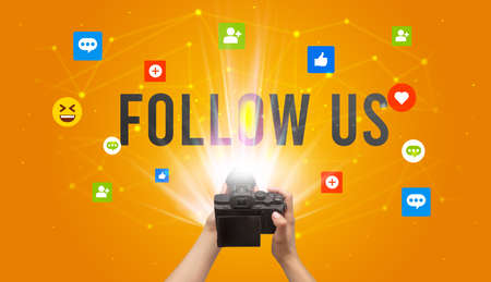 Using camera to capture social media content with FOLLOW US inscription, social media content concept