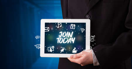 Young business person working on tablet and shows the inscription: JOIN TODAY Stockfoto
