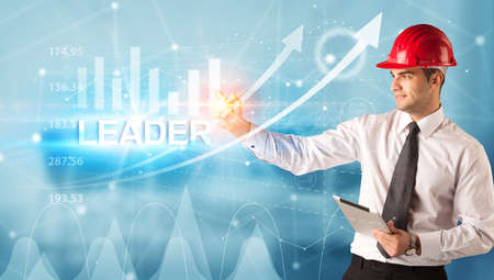 Young businessman with helmet drawing LEADER inscription, modern business technology concept 版權商用圖片