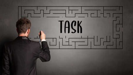 businessman drawing maze with TASK inscription, business education concept