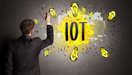 businessman drawing colorful light bulb with IOT abbreviation, new technology idea concept