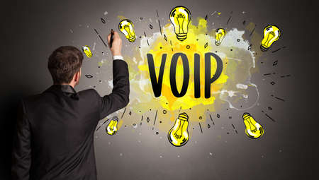 businessman drawing colorful light bulb with VOIP abbreviation, new technology idea concept