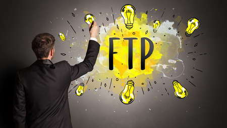 businessman drawing colorful light bulb with FTP abbreviation, new technology idea concept 版權商用圖片