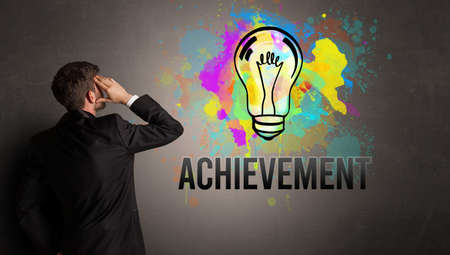 businessman drawing colorful light bulb with ACHIEVEMENT inscription on textured concrete wall, new business idea concept