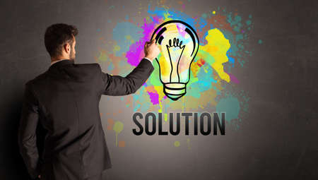 businessman drawing colorful light bulb with SOLUTION inscription on textured concrete wall, new business idea concept
