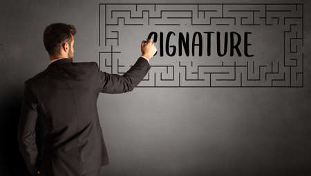 businessman drawing maze with SIGNATURE inscription, business education concept