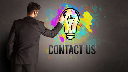 businessman drawing colorful light bulb with CONTACT US inscription on textured concrete wall, new business idea concept