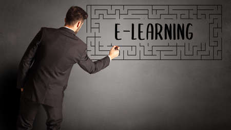 businessman drawing maze with E-LEARNING inscription, business education concept