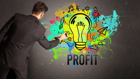 businessman drawing colorful light bulb with PROFIT inscription on textured concrete wall, new business idea concept
