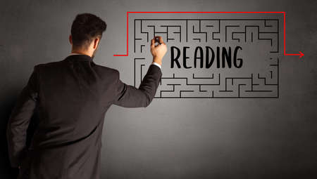 businessman drawing maze with READING inscription, business education concept