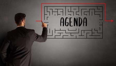 businessman drawing maze with AGENDA inscription, business education concept 版權商用圖片