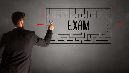 businessman drawing maze with EXAM inscription, business education concept