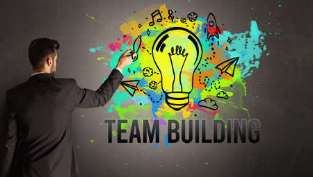 businessman drawing colorful light bulb with TEAM BUILDING inscription on textured concrete wall, new business idea concept