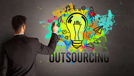 businessman drawing colorful light bulb with OUTSOURCING inscription on textured concrete wall, new business idea concept