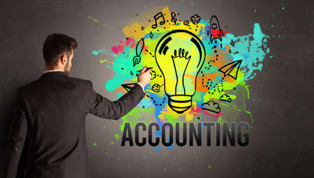 businessman drawing colorful light bulb with ACCOUNTING inscription on textured concrete wall, new business idea concept