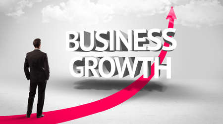Rear view of a businessman standing in front of BUSINESS GROWTH inscription, successful business concept
