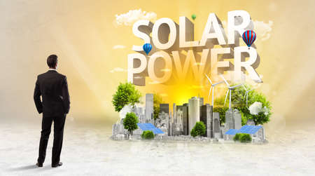 Rear view of a businessman standing in front of SOLAR POWER inscription, Environmental protection concept