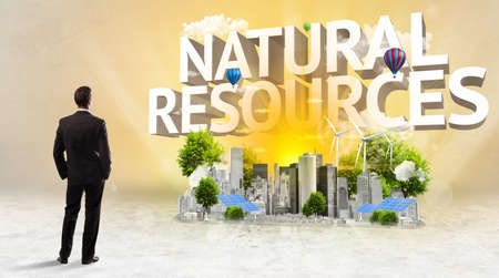 Rear view of a businessman standing in front of NATURAL RESOURCES inscription, Environmental protection concept