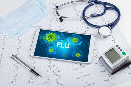 Close-up view of a tablet pc with FLU inscription, microbiology concept