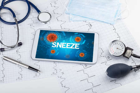 Close-up view of a tablet pc with SNEEZE inscription, microbiology concept
