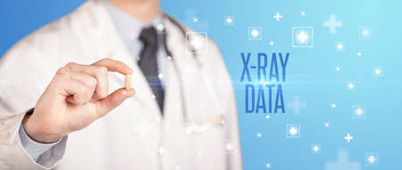 Close-up of a doctor giving a pill with X-RAY DATA inscription, medical concept Stock fotó