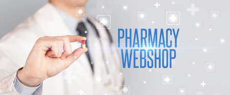 Close-up of a doctor giving a pill with PHARMACY WEBSHOP inscription, medical concept