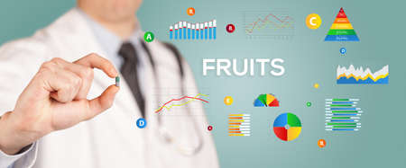 Nutritionist giving you a pill with FRUITS inscription, healthy lifestyle concept Stock fotó