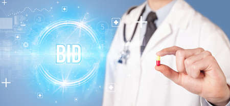 Close-up of a doctor giving you a pill with Bid abbreviation, virology concept