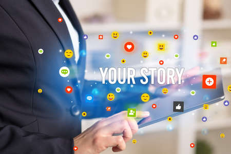 Close up of business person playing multimedia with social media icons and YOUR STORY inscription Фото со стока