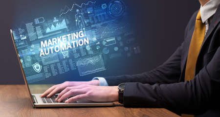Businessman working on laptop with MARKETING AUTOMATION inscription, cyber technology concept