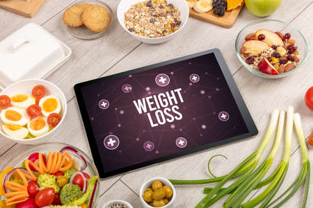 WEIGHT LOSS concept in tablet pc with healthy food around, top view