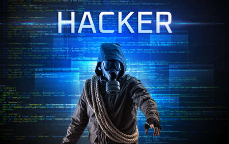 Faceless hacker with HACKER inscription on a binary code background Фото со стока