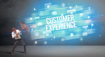 Handsome businessman defending with umbrella from CUSTOMER EXPERIENCE inscription, new age media concept